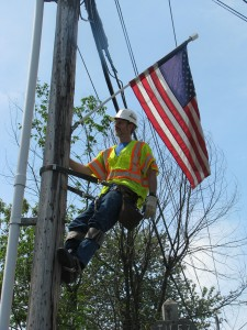 Employee hangs flag for Memorial Day celebration in Waitsfield.